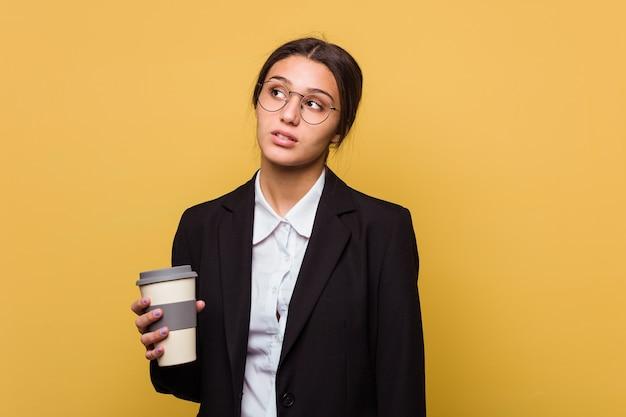 孤立した持ち帰りのコーヒーを飲む若いインドのビジネス女性