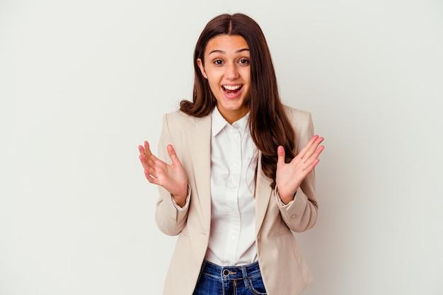 승리 또는 성공을 축 하하는 흰 벽에 고립 된 젊은 인도 비즈니스 여자, 그는 놀라게 하 고 충격.