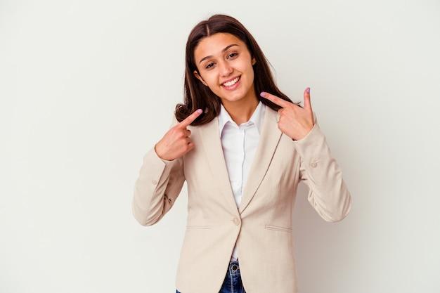 입에서 손가락을 가리키는 흰 벽 미소에 고립 된 젊은 인도 비즈니스 여자.