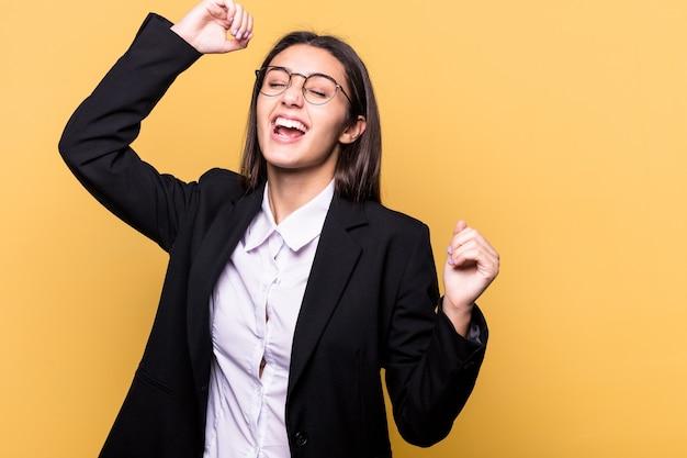 Молодая индийская бизнес-леди изолирована на желтой стене, празднует особый день, прыгает и поднимает руки с энергией