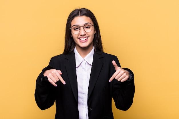 黄色の壁に孤立した若いインドのビジネス女性が指で下向き、前向きな気持ち