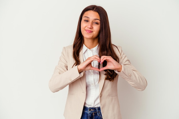 Young indian business woman isolated on white smiling and showing a heart shape with hands.