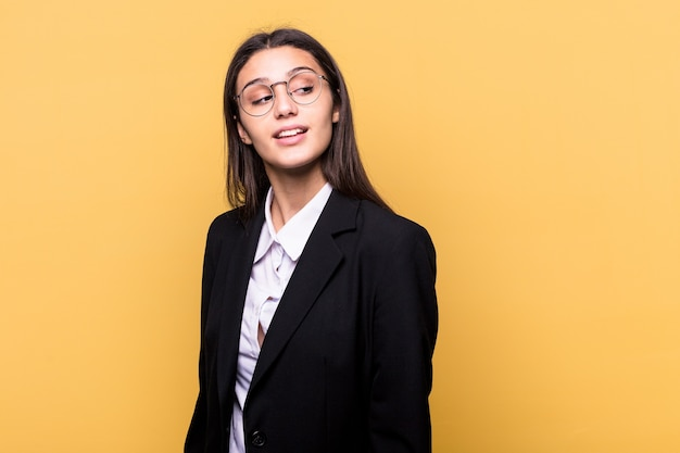 Young indian business woman isolated on yellow background looks aside smiling, cheerful and pleasant.