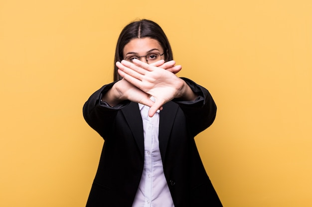 Young indian business woman isolated on yellow doing a denial gesture