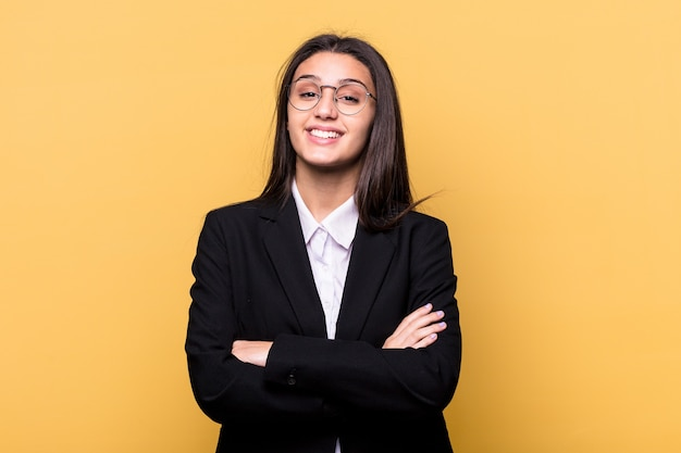 Young indian business woman isolated on yellow wall who feels confident, crossing arms with determination