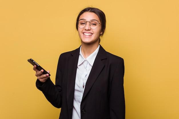 黄色の壁で隔離の電話で話している若いインドのビジネス女性