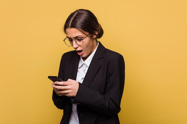 Young indian business woman talking on phone isolated on yellow wall