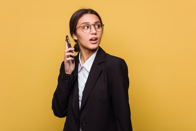 Young indian business woman talking on phone isolated on yellow