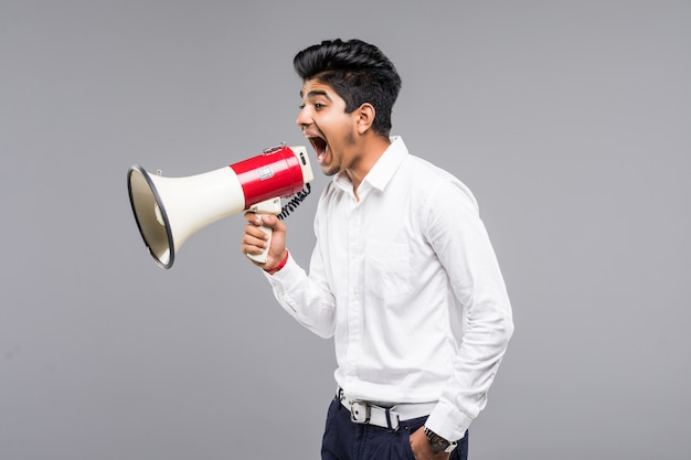 Young indian businessman announcing into a megaphone on gray wall