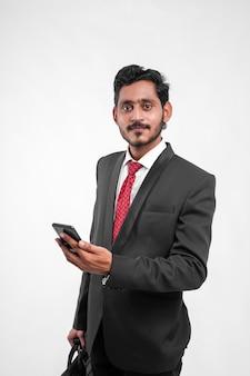 Молодой индийский бизнесмен, держа в руке сумку для ноутбука и используя мобильный телефон
