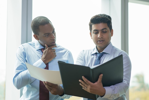 Young indian businessman reading document aloud for coworker