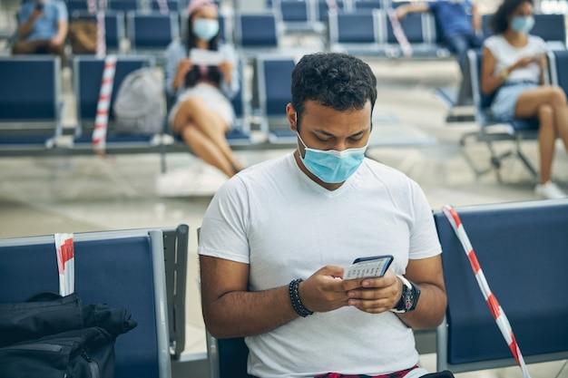 国際空港の待合室で座ってスマートフォンを使用して若いインド人実業家