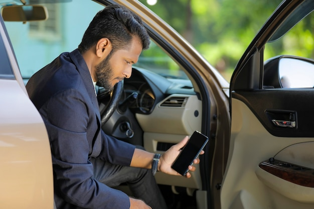 Young indian businessman sitting in side of car and showing smart phone screen