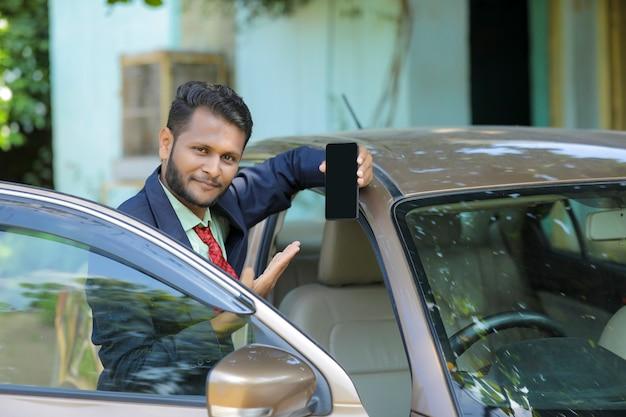 車の横に立ってスマートフォンの画面を表示している若いインド人実業家