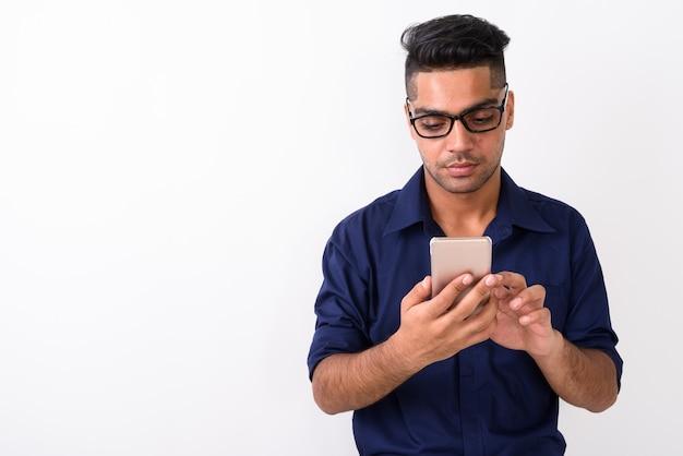 Молодой индийский бизнесмен с помощью мобильного телефона на белом