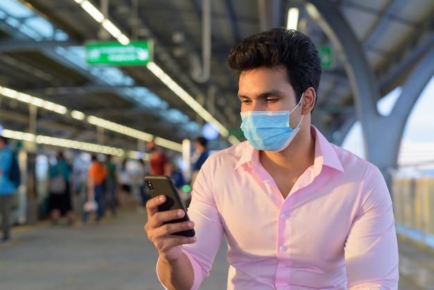 スカイトレインの駅で電話を使用しながらマスクを着用し、距離を置いて座っている若いインドのビジネスマン