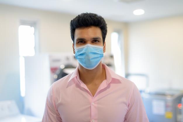 屋内で洗濯をしながらマスクを身に着けている若いインド人実業家