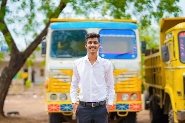 Молодой индийский бизнесмен с его грузовиком или грузовиком вперед.