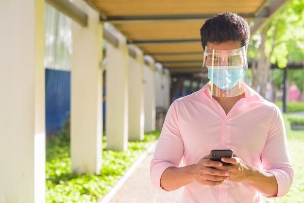 Молодой индийский бизнесмен с маской и щитком для лица, используя телефон в парке на открытом воздухе