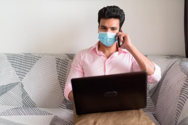 Молодой индийский бизнесмен с маской разговаривает по телефону, используя ноутбук дома в карантине