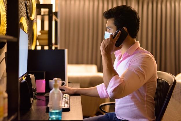 검역 기간 동안 집에서 초과 근무하는 동안 전화로 얘기하는 마스크와 젊은 인도 사업가
