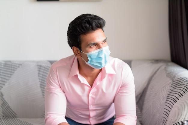 Молодой индийский бизнесмен с маской думает в гостиной и сидит дома в карантине