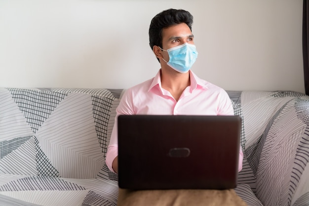 Молодой индийский бизнесмен с маской думает, используя ноутбук и остается дома на карантине