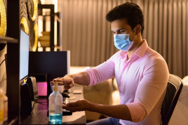 Молодой индийский бизнесмен с маской, используя дезинфицирующее средство для рук, работая сверхурочно дома во время карантина