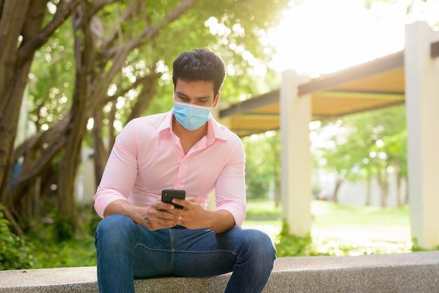 Молодой индийский бизнесмен с маской, используя телефон и сидя в парке
