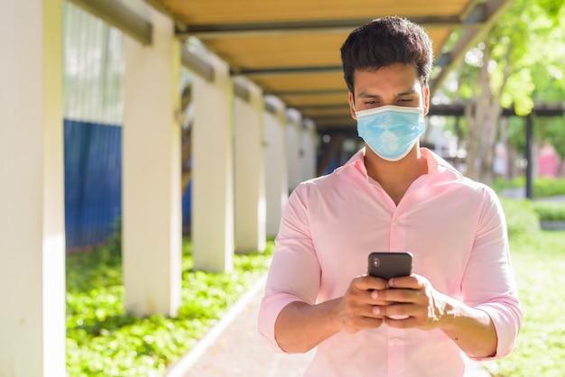 Молодой индийский бизнесмен с маской, используя телефон в парке