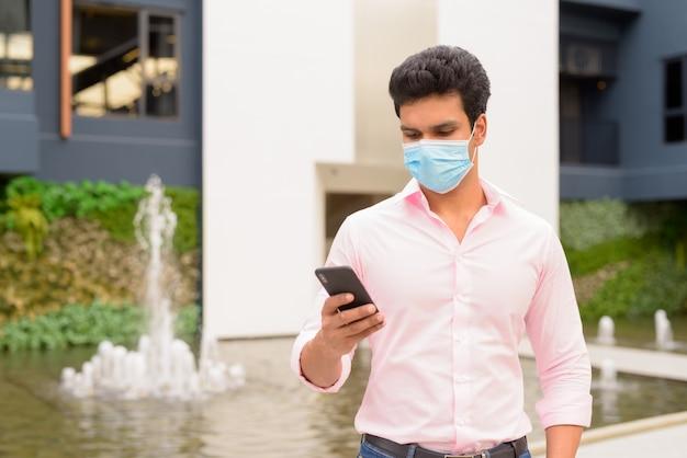 Молодой индийский бизнесмен с маской, используя телефон в городе на открытом воздухе