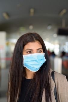 스카이 트레인 역에서 생각하는 코로나 바이러스 발생으로부터 보호하기 위해 마스크가있는 젊은 인도 사업가