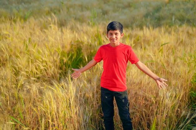 インド農村部の麦畑で遊ぶ若いインド人の子供