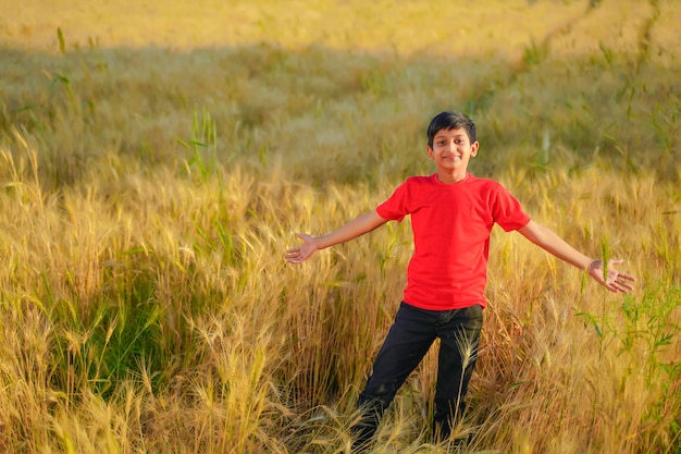 Young indian child playing at wheat field
