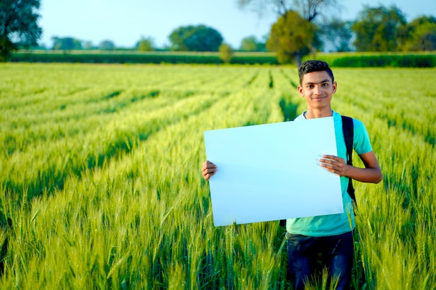 インドの麦畑で空白のポスターを持つ若いインド人の子供