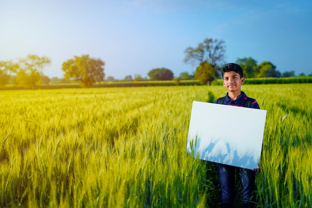 Young indian child with blank poster at indian wheat field