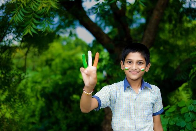 顔にインドの旗を持つ若いインドの子供