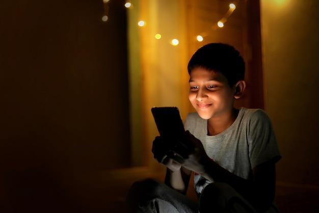 Молодой индийский ребенок со смартфоном