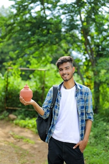 Young indian college boy holding clay piggy bank in hand over nature background