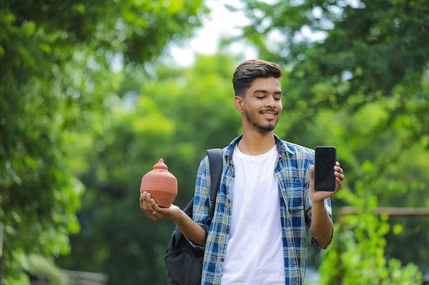 Молодой индийский мальчик колледжа держит в руке глиняную копилку на фоне природы