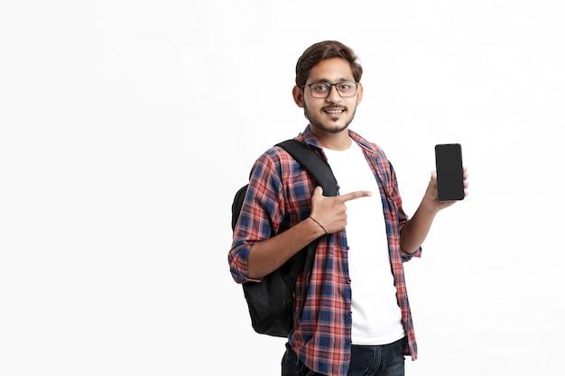 白い壁にスマートフォンの画面を表示する若いインドの大学生