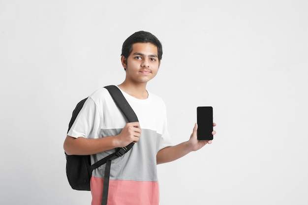 Young indian college student showing smartphone screen on white wall