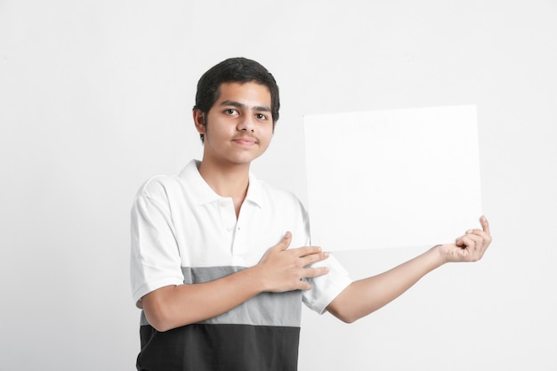 Young indian college student showing white board on white wall