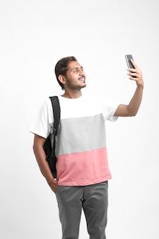 Молодой индийский студент колледжа, делающий селфи с мобильным телефоном
