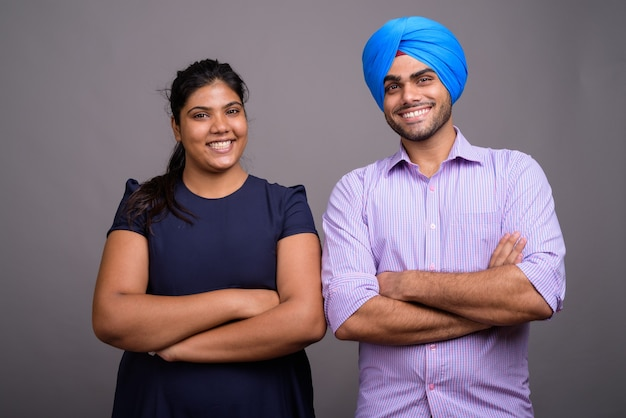 Young indian couple together and in love against gray wall