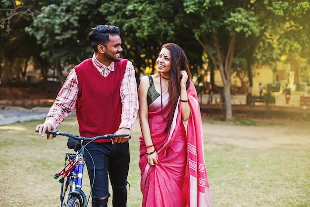 Young indian couple in traditional ethnic clothes walking with the bicycle