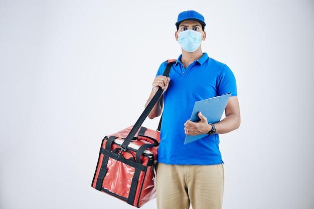 白で隔離のクーラーバッグで食品を配達する医療マスクの若いインドの宅配便
