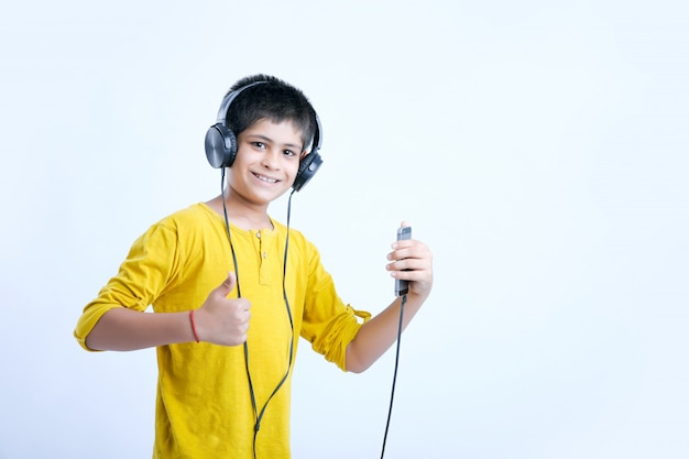 Young indian cute boy listening music in headphone