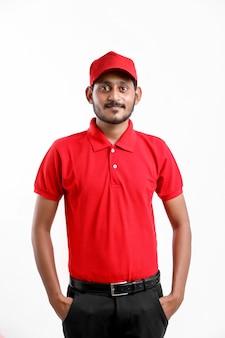 白い背景の上に表情を示す若いインドの配達少年。