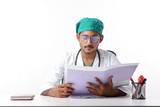 クリニックでファイルをチェックする若いインド人医師